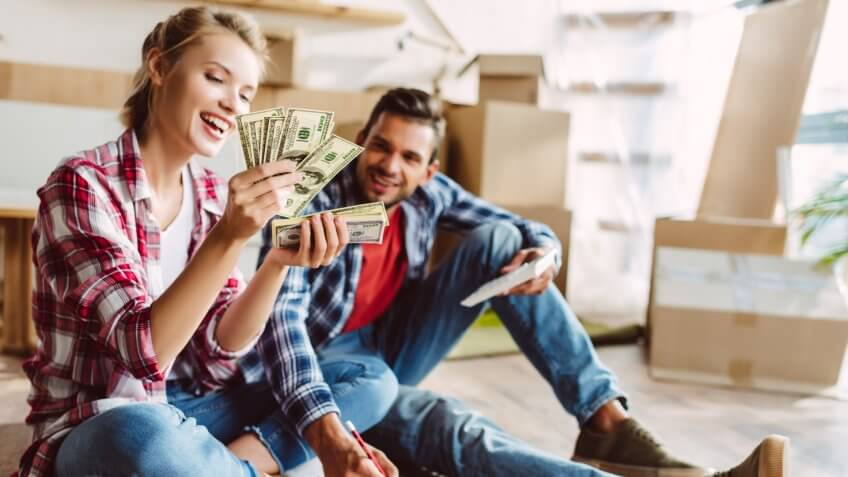happy young couple with calculator and dollar banknotes counting money in new apartment.