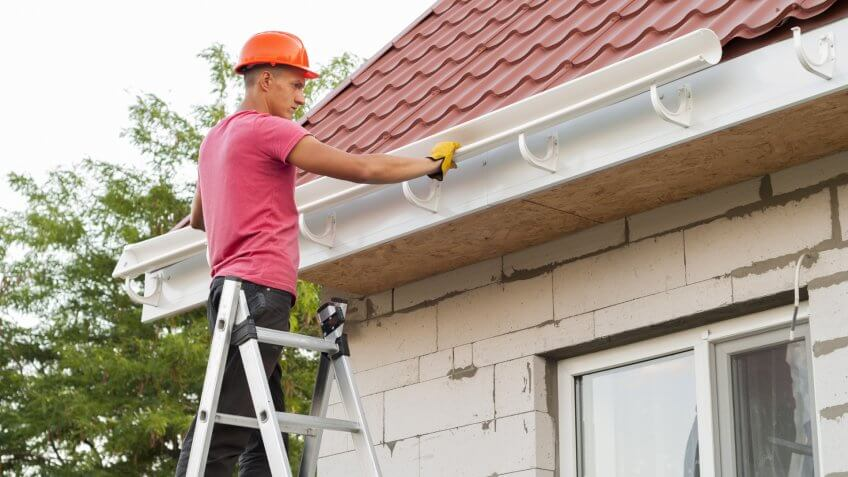 worker installs the gutter system on the roof.