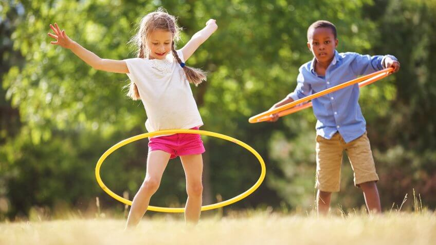 Girl and boy with hula hoop playing at the park.