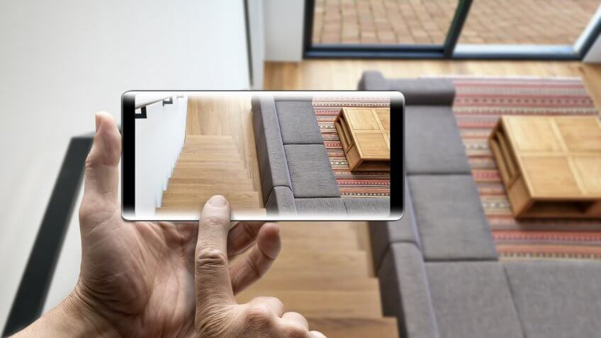 Two hands holding a mobile Smartphone taking picture on Hardwood stairs and ramp in modern renovated living room.