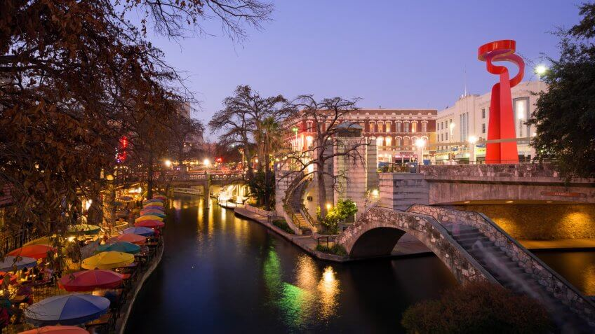 San Antonio, United States - February 18, 2014: People meander about the River Walk during the nighttime while others dine at the restaurant of Casa Rio next to the water.
