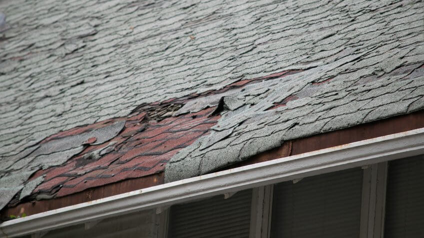 Roof of a residential house showing damage to the tile and gutter systems, multiple layers of shingles, missing shingles, and rusty gutters.