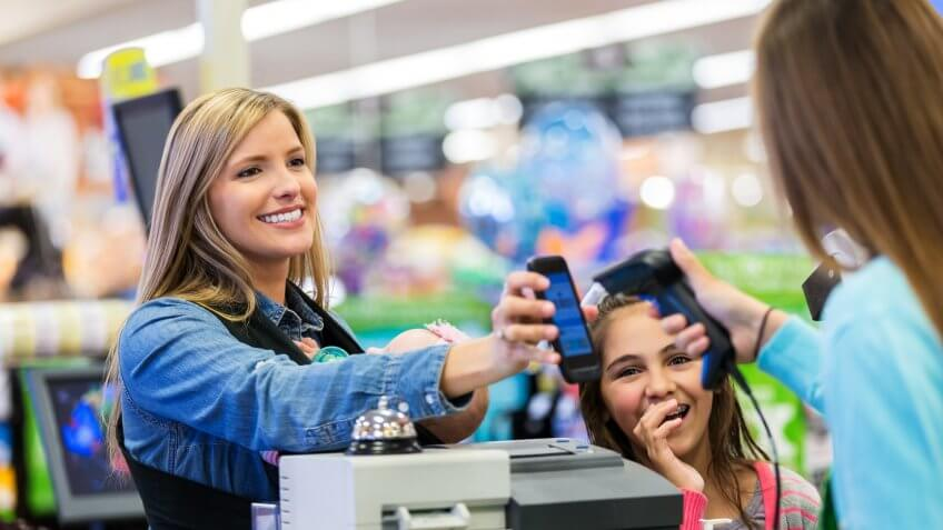 Mid adult Caucasian woman is using her smart phone app to pay for groceries in local grocery store.