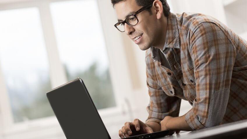 A man sitting using a laptop computer.
