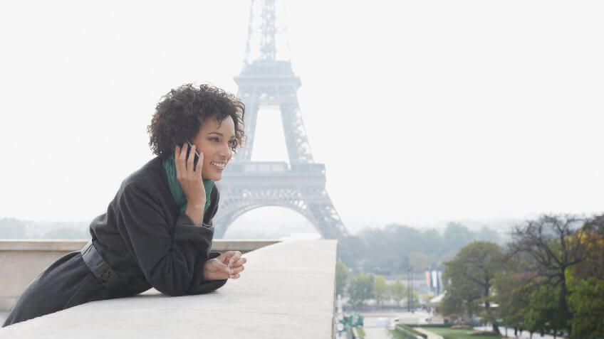 Woman outdoors on her mobile phone by the Eiffel Tower.