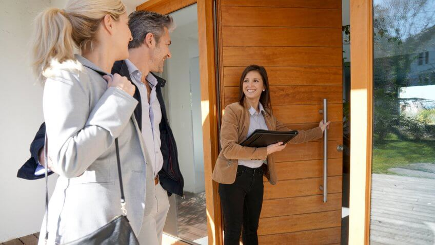Real estate agent inviting couple to enter house for visit.