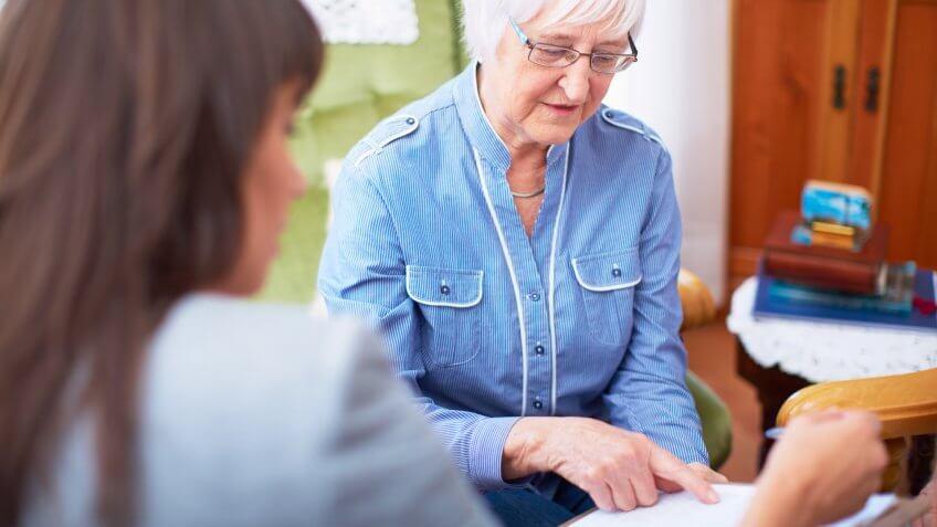 Woman explaining document to senior woman.