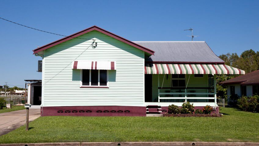 Tidy little old style house with clear blue sky and green grass and overhead power line connected to it – Queensland Australia.