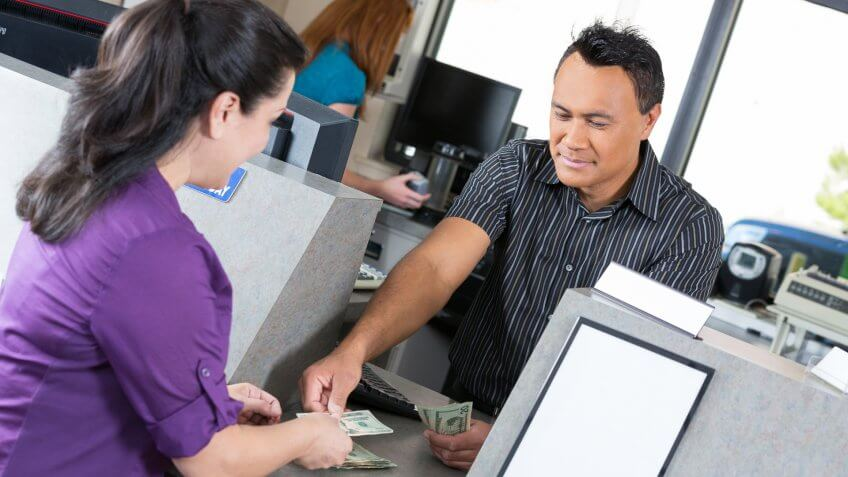 Customer at the bank getting money from the teller.