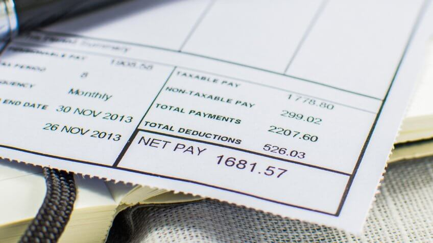 Wage slip on pad with black pen.