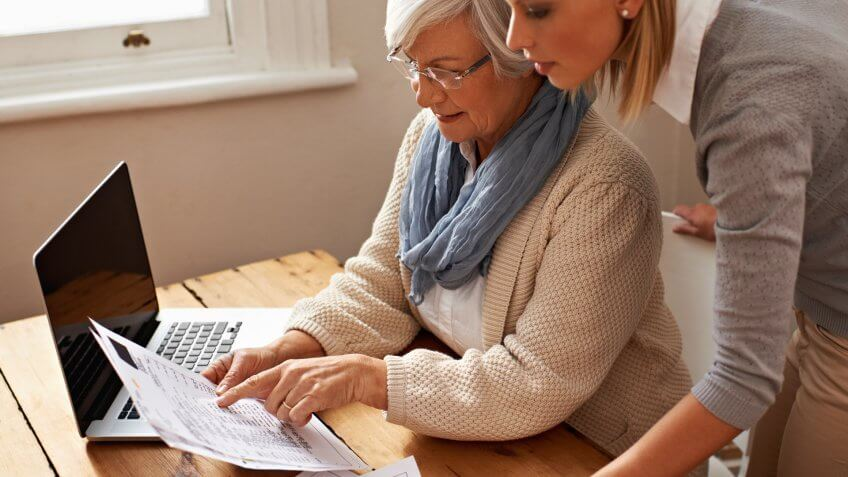 Cropped view of a senior woman receiving help with her finances from her granddaughter.