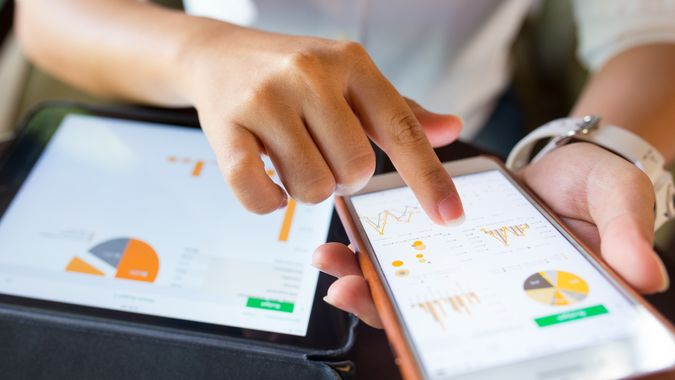 Businesswoman check data in smartphone and tablet.
