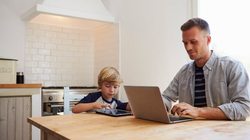 father on computer next to son