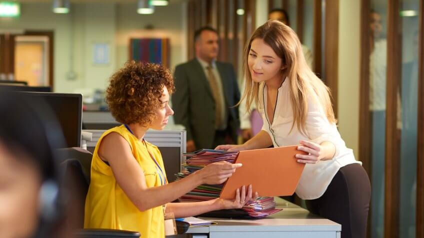 a young office junior takes a file from her supervisor for filing in a large open plan office .
