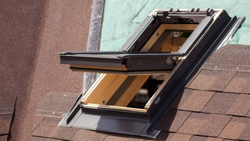 Open skylight on a roof shingles under construction.