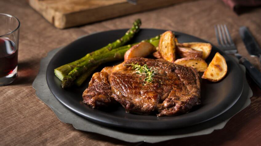 Grilled ribeye steak with asparagus and steak fries in a low-key, rustic country setting.