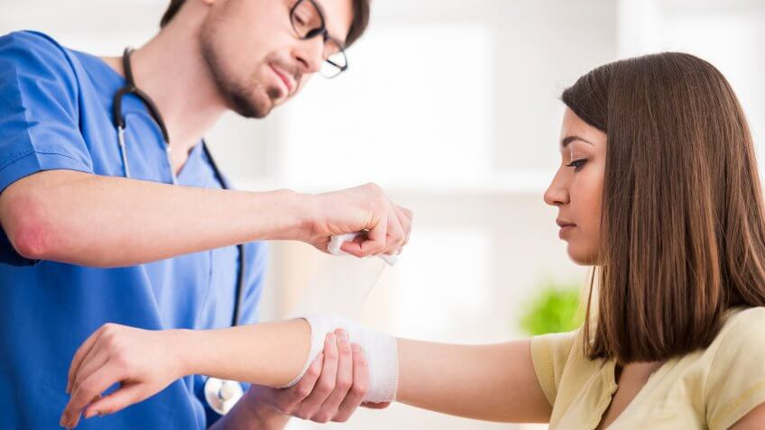 Confident male doctor is bandaging upper limb of young woman.