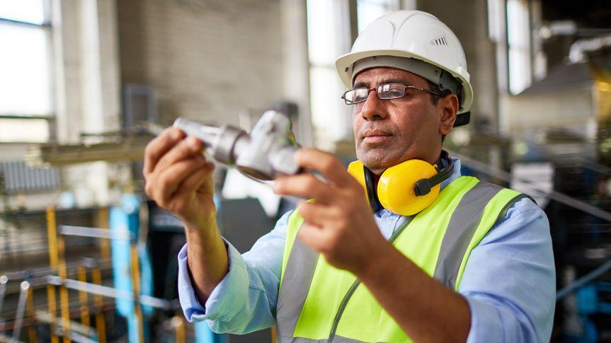 Manufacturing engineer examining pipe