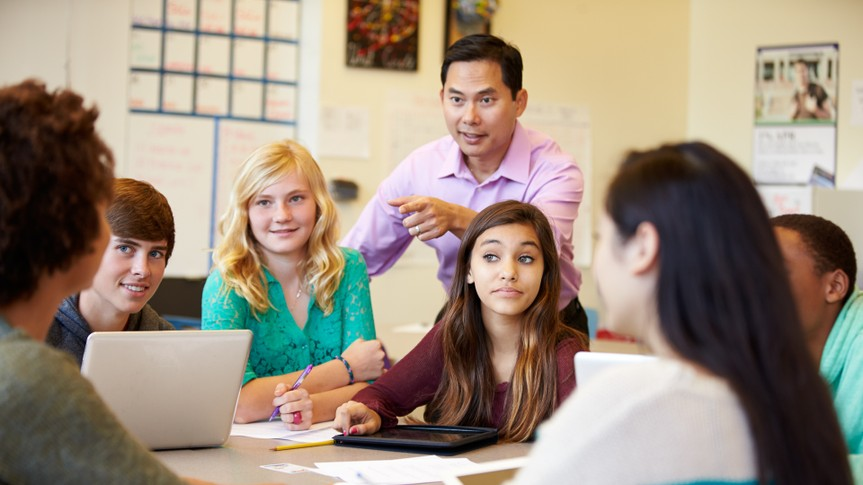 High School Students With Teacher In Class Using Laptops Smiling.