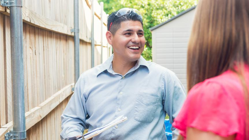 Mid adult Hispanic man is repairman or insurance agent.