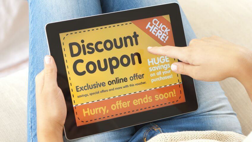 Woman using a discount coupon on a digital tablet on the sofa.