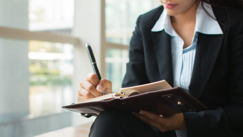 business woman taking notes in a planner with a pen