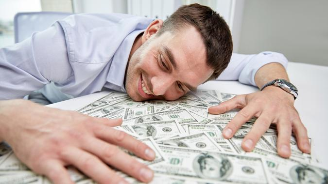 business, people, success and fortune concept - happy businessman with heap of dollar money in office.