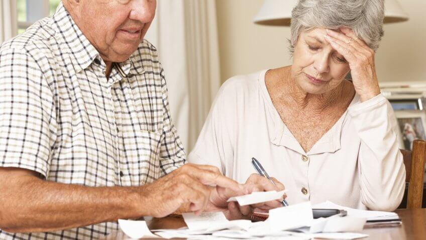 Senior Couple Concerned About Debt Going Through Bills Together.