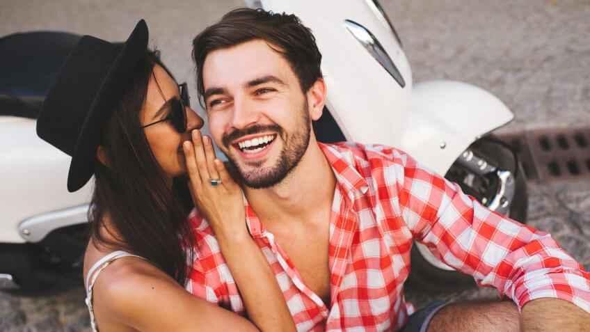 Close up of attractive young couple whipsering to ear a secret while sitting near scooter and smiling.