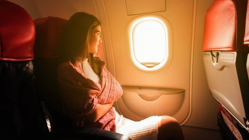 Young beautiful woman sit by window of airplane during flight.