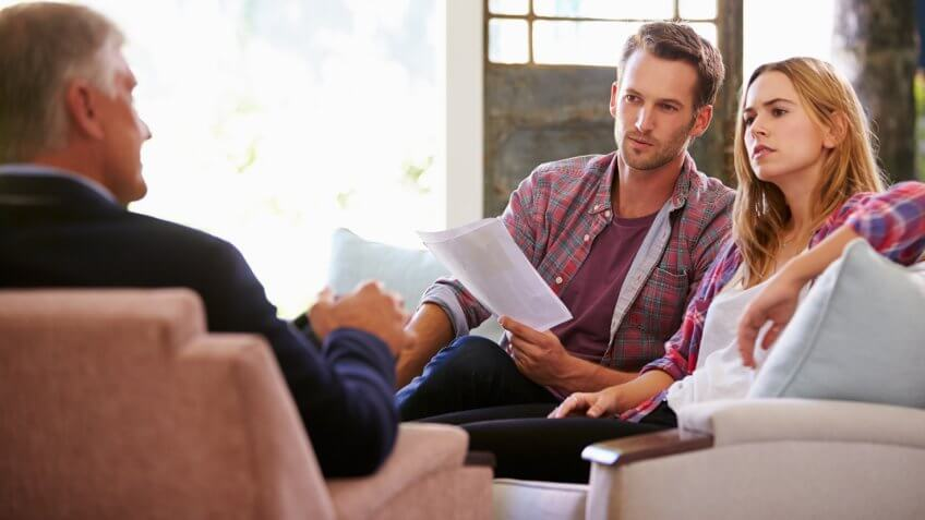 Couple At Home Meeting With Financial Advisor.