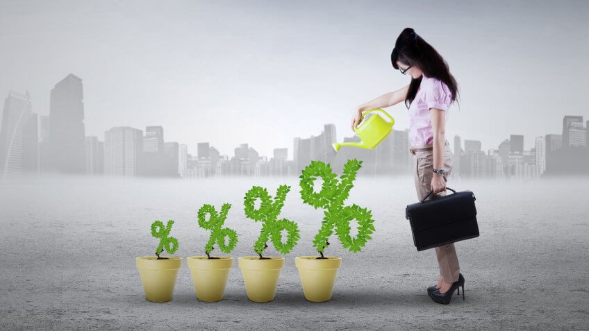 Image of successful young woman with plant on the pots shaped percentage symbol.