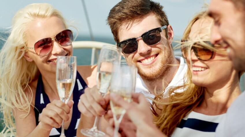 vacation, travel, sea, friendship and people concept - smiling friends with glasses of champagne on yacht.