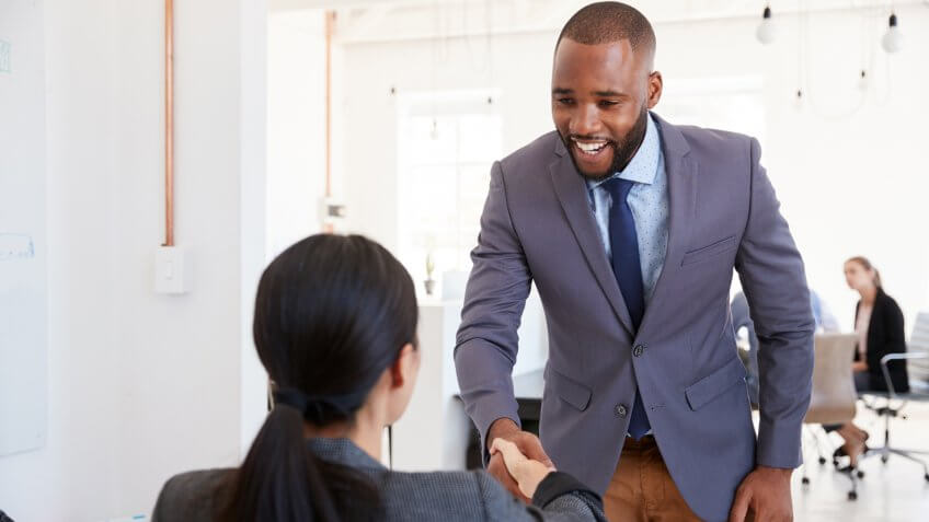 Black businessman and seated woman shaking hands in office.