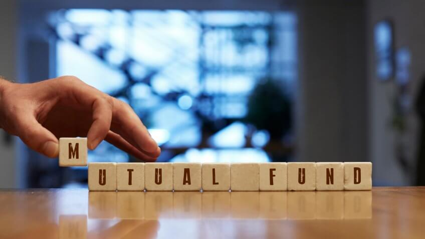 Mutual Fund Concept , Hand with alphabet blocks on wooden table.