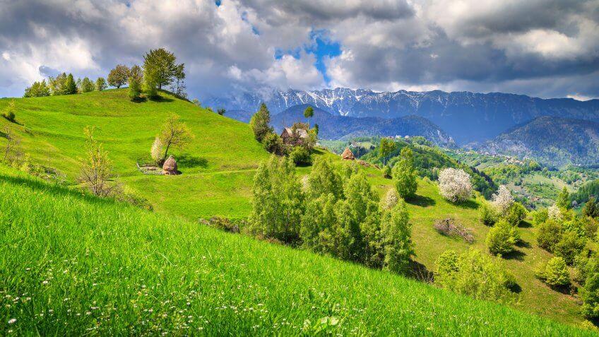 Spring alpine landscape with green fields, Magura village, Transylvania, Romania, Europe.