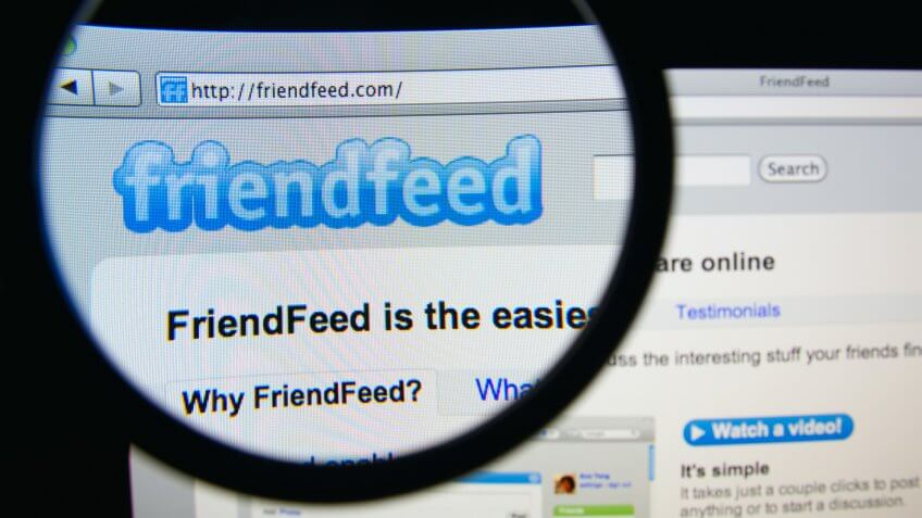 LISBON, PORTUGAL - FEBRUARY 19, 2014: Photo of FriendFeed homepage on a monitor screen through a magnifying glass.