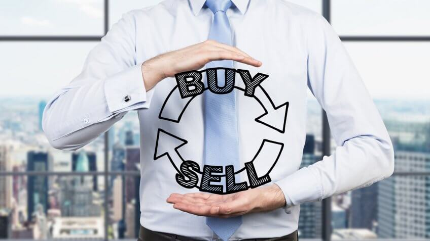 Businessman is holding a trading concept in his hands.