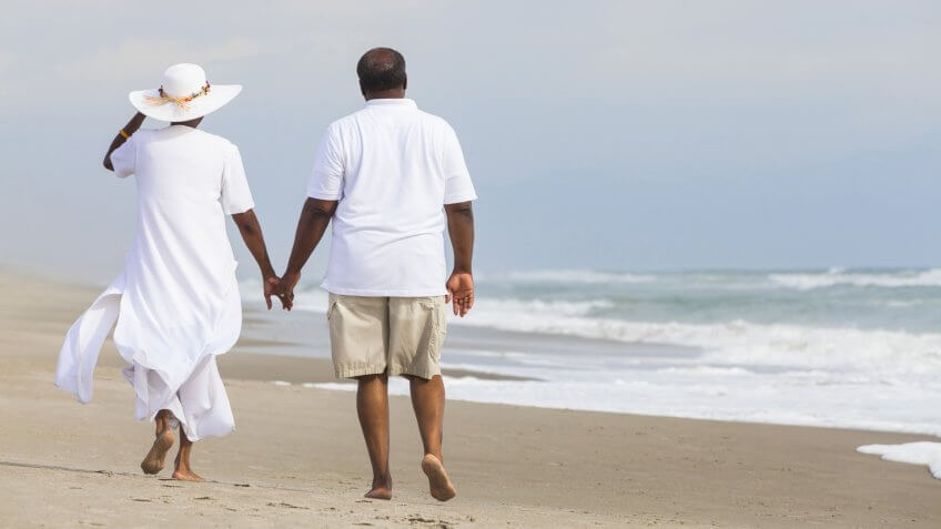 couple walking holding hands on a deserted tropical beach