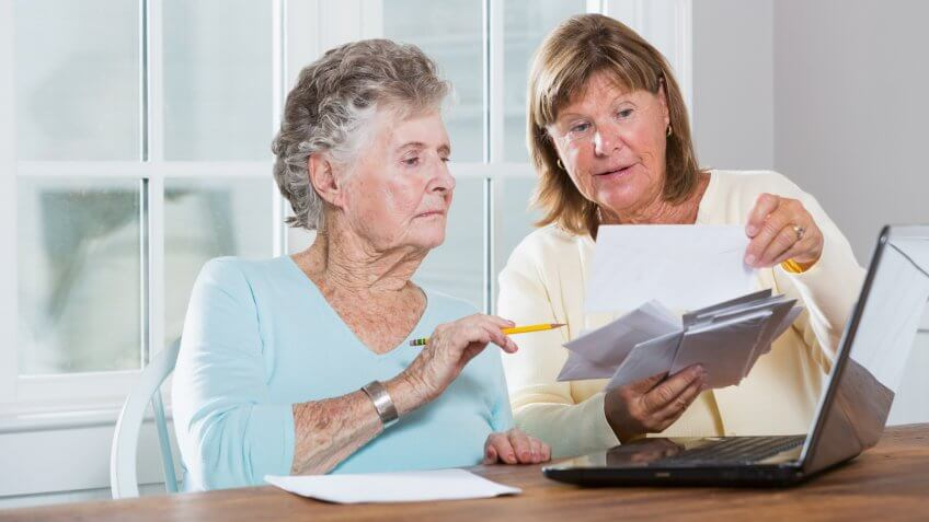 Mature woman (60s) helping elderly mother (90s) pay bills.