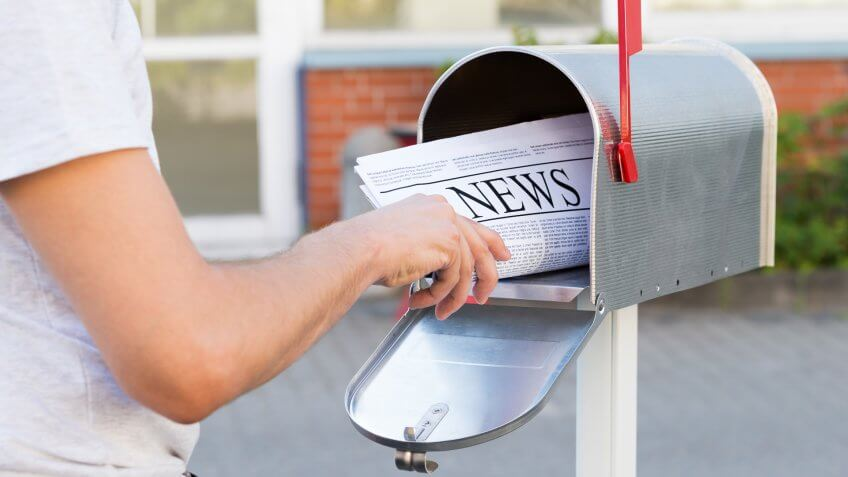 Close-up Of Person Hands Opening His Mailbox To Remove Newspaper.
