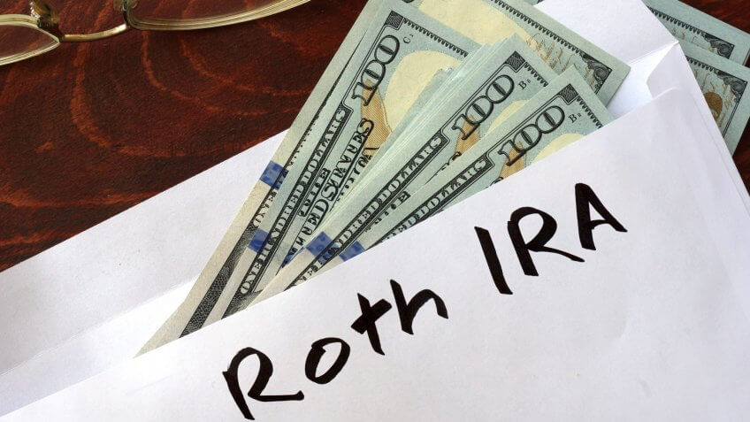 Roth IRA written on an envelope with dollars.