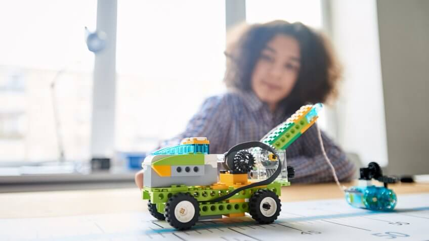 Close-up shot of toy lifting truck and smaller car made of plastic building blocks following blue line one after another, teenage boy looking at them with smile in classroom.