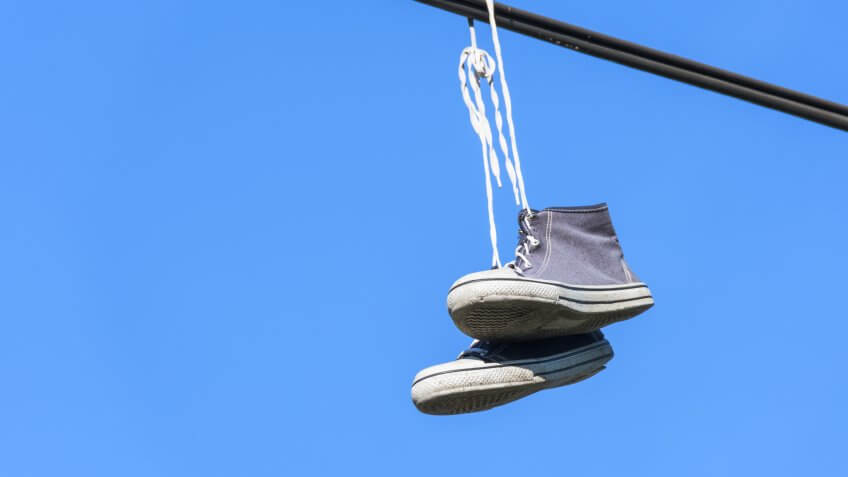A pair of blue high converse sneakers suspended on a stick.
