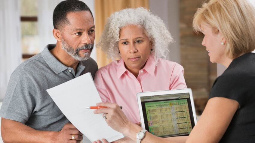 Older couple consulting with financial planner.