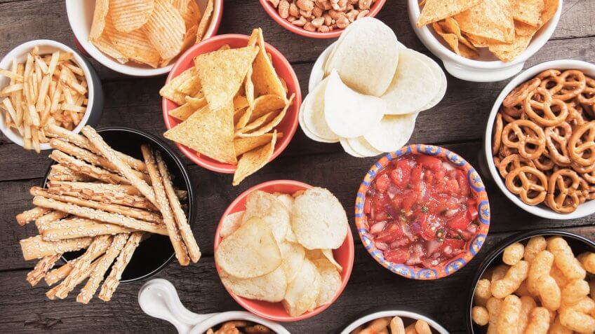 Salty crackers, tortilla chips and other savory snacks with salsa dip.
