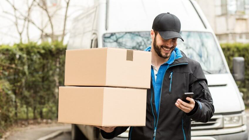 delivery man holding boxes checking smartphone