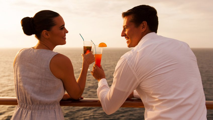 romantic young couple toasting with cocktail on cruise ship.
