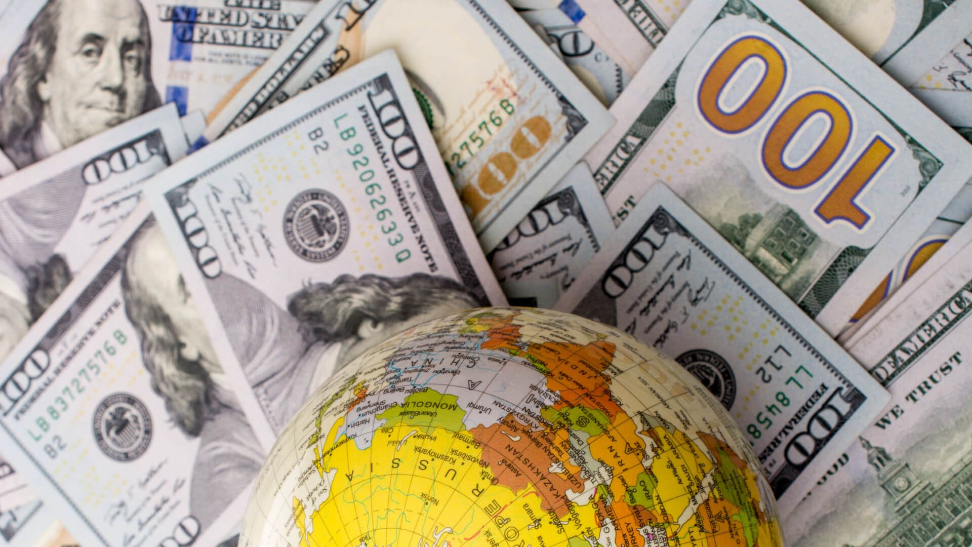 Model globe is placed on spread US dollar banknotes.