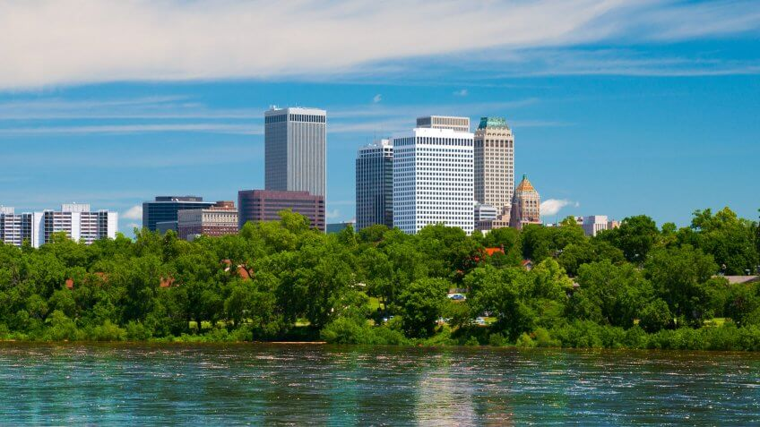Tulsa downtown skyline with trees and the Arkansas river in the foreground.
